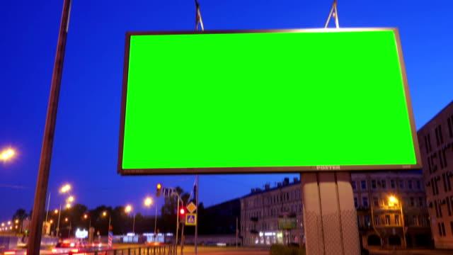 ein plakat mit einem green-screen in einer anstrengenden nacht straße - poster stock-videos und b-roll-filmmaterial