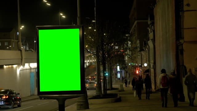 a billboard with a green screen on a busy street. people walk along the sidewalk, - banner internetowy filmów i materiałów b-roll