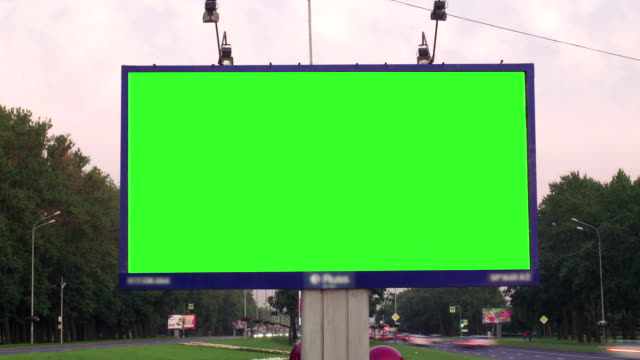 ein plakat mit einem grünen bildschirm an einer verkehrsreichen strasse - poster stock-videos und b-roll-filmmaterial