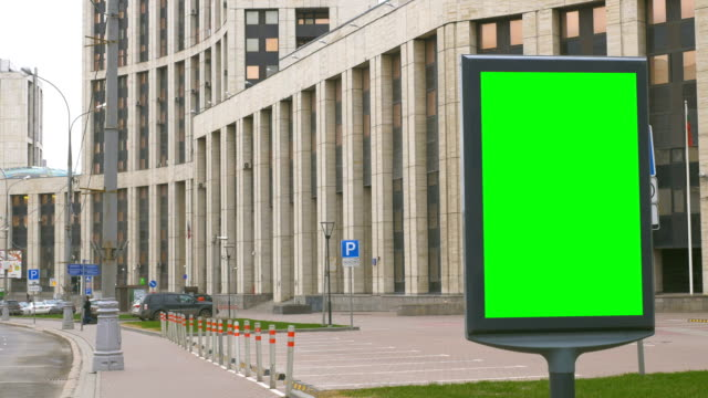 a billboard with a green screen on a busy street. - poster стоковые видео и кадры b-roll