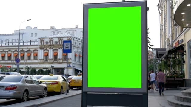 vídeos y material grabado en eventos de stock de un cartel con una pantalla verde en una calle muy transitada. - póster