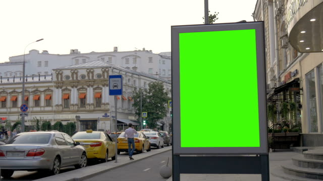 A Billboard with a Green Screen on a Busy Street. A Billboard with a Green Screen on a Busy Street. People and tourists are walking on a summer day. billboard stock videos & royalty-free footage