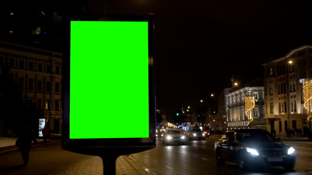 Billboard with a green screen on the street decorated for the holiday. Billboard with a green screen on the street decorated for the holiday. In evening time billboard stock videos & royalty-free footage