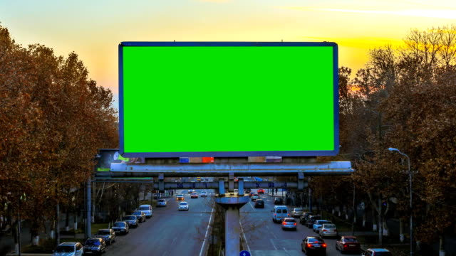 vídeos de stock e filmes b-roll de a billboard with green chroma key on the background of fast moving cars at sunset - faixa sinal