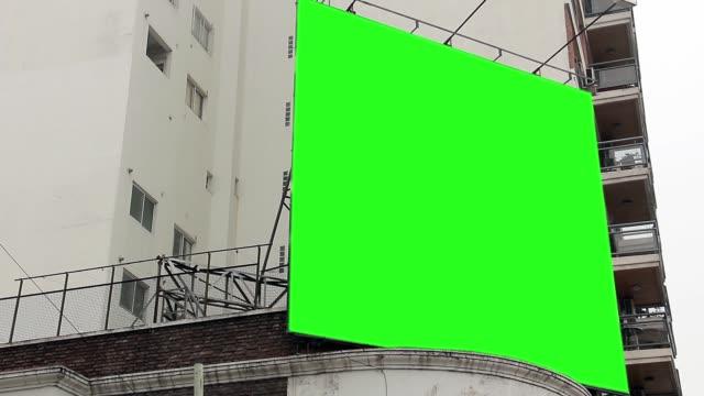 plakatwand mit greenscreen auf ein gebäude. - poster stock-videos und b-roll-filmmaterial