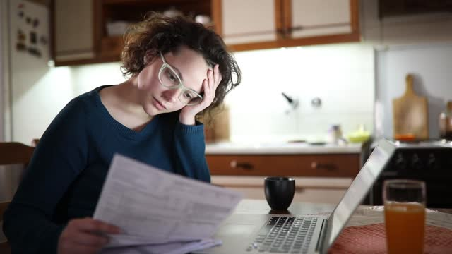 Bills give her headache Woman going through bills, looking worried. Young brunette curly female reading her bill papers and getting headache from stress. bills and taxes stock videos & royalty-free footage