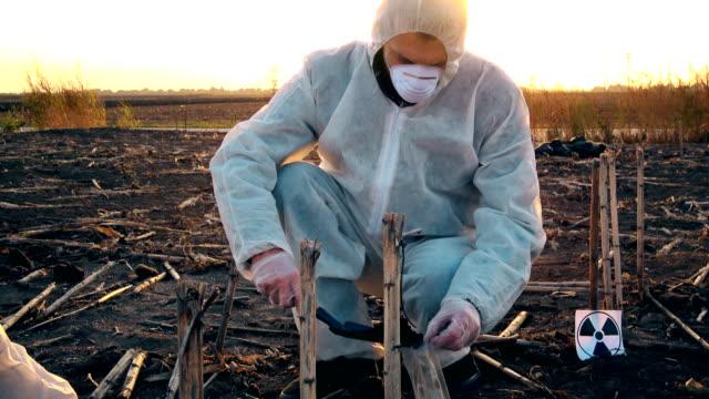 Bio hazard scientist examining soil disease video