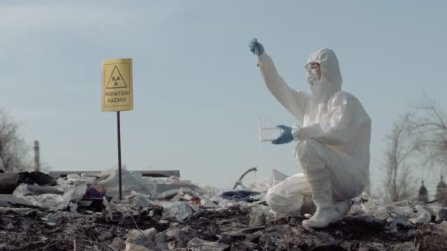 biological hazard, woman scientist ecologist in uniform and protective gloves taking sample of the garbage from big dirty dump