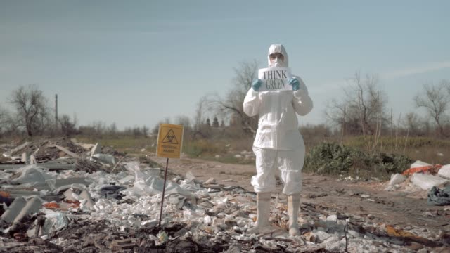 biological hazard, young woman in uniform and protective glasses holding poster think green standing at trash dump in rubber boots near sign
