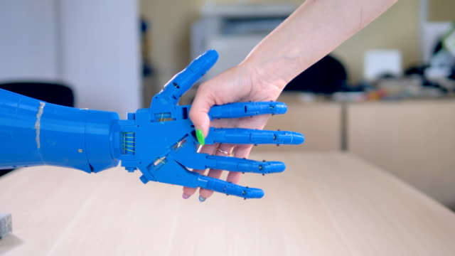 A bionic hand being shaken by a human female one. A woman manicured hand shacking a blue robotic arm. cyborg stock videos & royalty-free footage
