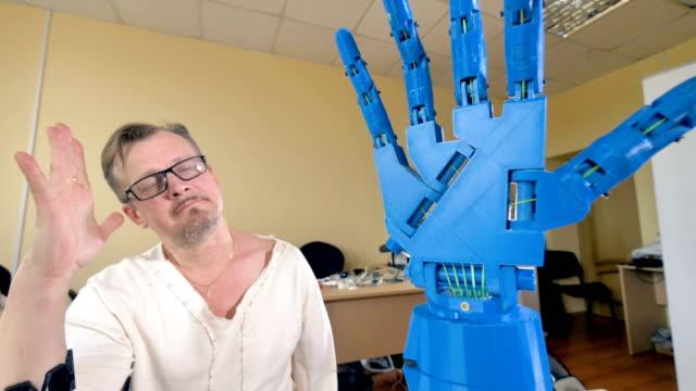 vídeos y material grabado en eventos de stock de mano robótica biónica repitiendo movimientos de la mano del hombre. close-up. - copiar