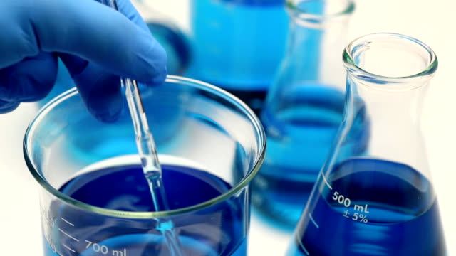 Biotechnology Research This is a close up photo of a scientist stirring a blue liquid in a beaker beaker stock videos & royalty-free footage