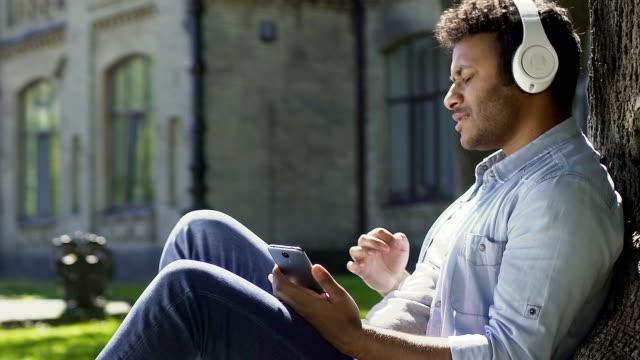 biracial guy listening to favorite radio station enjoying sound in headphones - adulazione video stock e b–roll