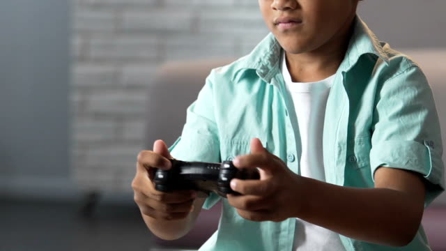 Biracial male kid playing video games at home, isolation from world, friendless Biracial male kid playing video games at home, isolation from world, friendless autism stock videos & royalty-free footage