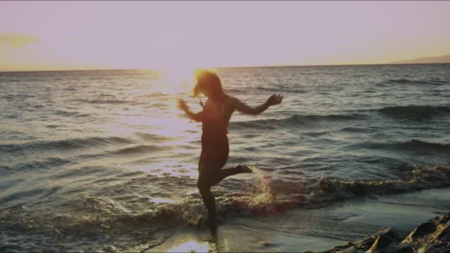 stockvideo's en b-roll-footage met een bi-rassen vrouw spelen in de oceaan. - mid volwassen vrouw