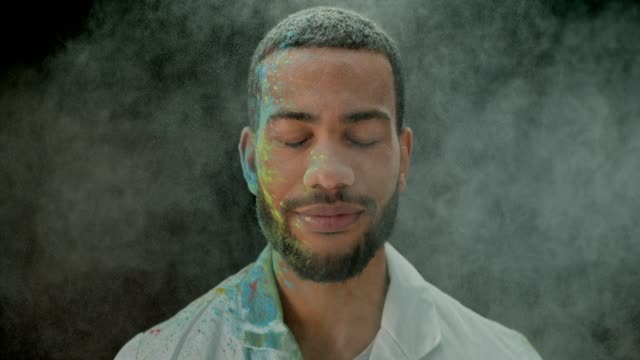 SLO MO Biracial young man with beard smiling with his eyes closed while in the cloud of colored powder Slow motion medium locked down shot of a young biracial man with a beard smiling in a cloud of colored dust with his eyes closed. Shot in Slovenia. eyes closed videos stock videos & royalty-free footage