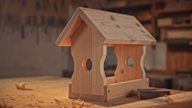 bird house set on the working table in the carpenter's shop - warsztat filmów i materiałów b-roll
