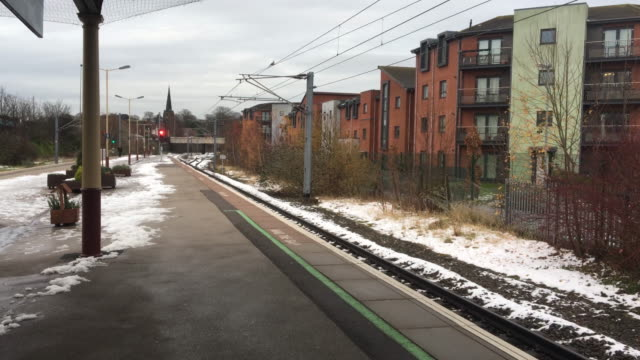 Bird swoops across a deserted train platform on a winters day video