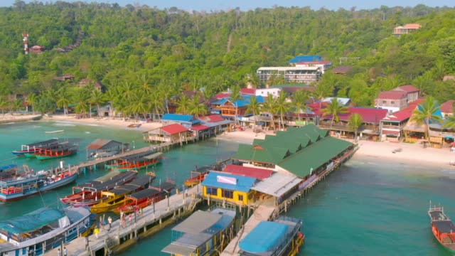 birds eye landscape of pier and colorful long tail boats nearby the ocean in koh rong island near sihanoukville in cambodia - cambogia video stock e b–roll