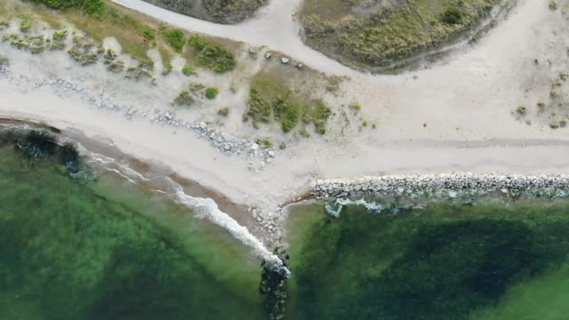 Birds eye view of a beach with groynes installed along its length to protect the coast from erosion. Golden sand builds up along the shore