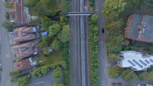 bird's eye view of a commuter train departing a station - intercity filmów i materiałów b-roll
