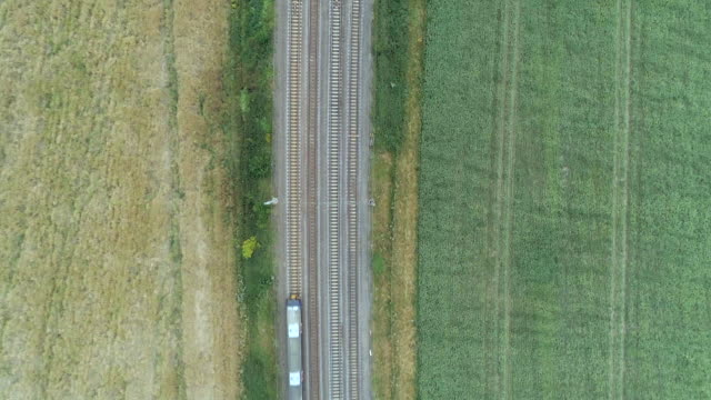 Bird's Eye View of a Commuter Train in the Countryside A fast commuter train is seen travelling through the English countryside on a route serving Central London railroad track stock videos & royalty-free footage