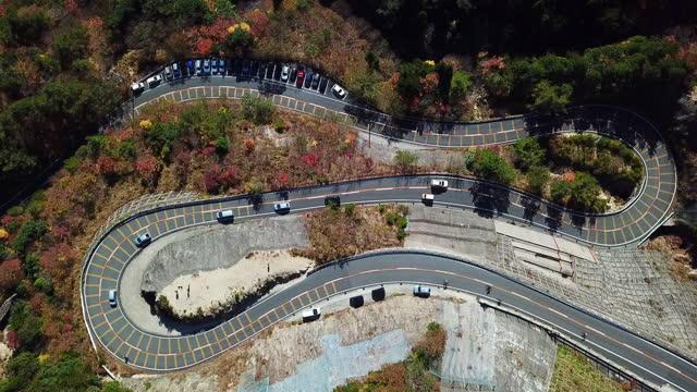 una vista a occhi di uccelli di un passo di montagna in autunno - strada tortuosa video stock e b–roll