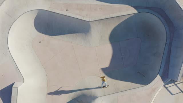 Birds eye view of a skateboarder riding in a concrete skatepark