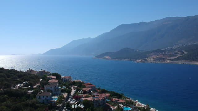Birds eye view of beautiful turquoise Mediterranean Sea at Kas, Antalya. Birds eye view of beautiful turquoise Mediterranean Sea at Kas, Antalya. Summer houses and villas with pools at the coast and green forests at the horizon. aegean sea stock videos & royalty-free footage