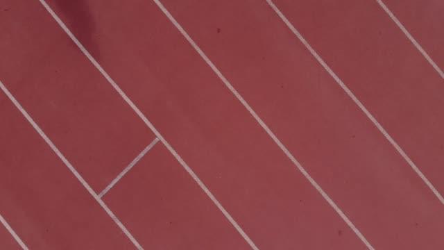 kadın atlet spor yolda çalışan kuş bakışı - pist stok videoları ve detay görüntü çekimi