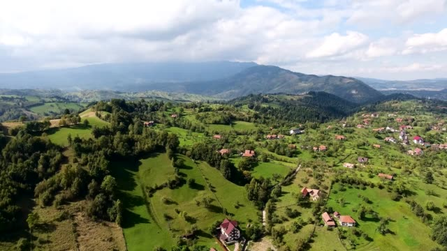 Birds eye view of Transylvania Mountains Romania. Bran City, Castle of Count Dracula Drone flies over the ancient buildings in the highlands. Clear sky. The houses are located in the valleys and all are built in the same style. Green meadows around and forest. Light clouds cover the tops of the mountains. vampire stock videos & royalty-free footage