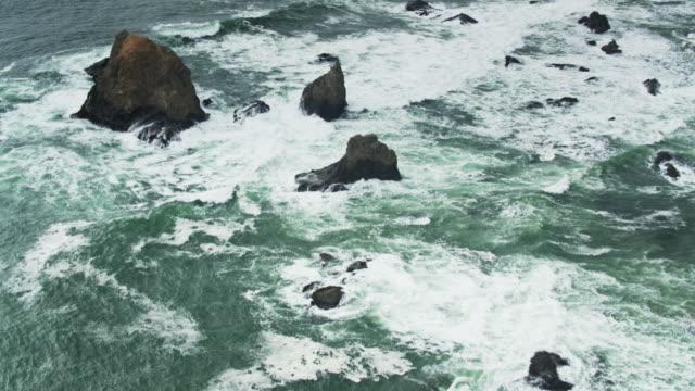 vídeos de stock e filmes b-roll de bird's eye view of waves swirling around rocks on the northern california coast - montanha costeira