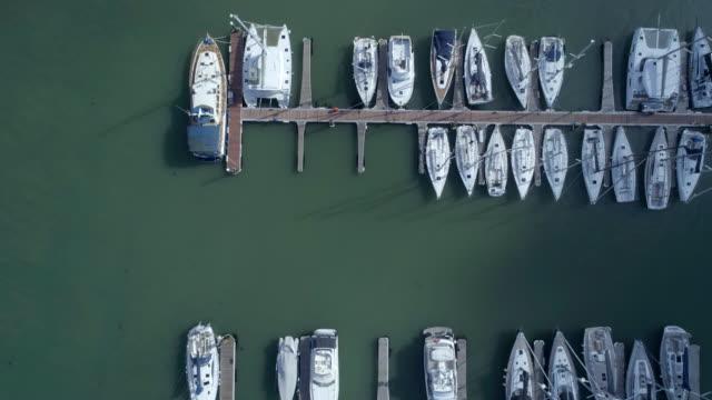 vídeos y material grabado en eventos de stock de a vista de pájaro de yates, barcos y embarcaciones de un puerto deportivo - amarrado