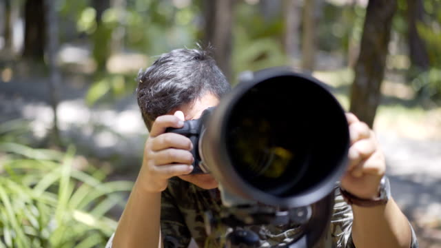 Birdwatcher taking photo of bird video