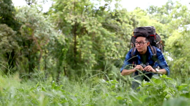 BirdWatching. Excited young man BirdWatcher use binolcular in rain forest background. Chiang Mai, Thailand.
