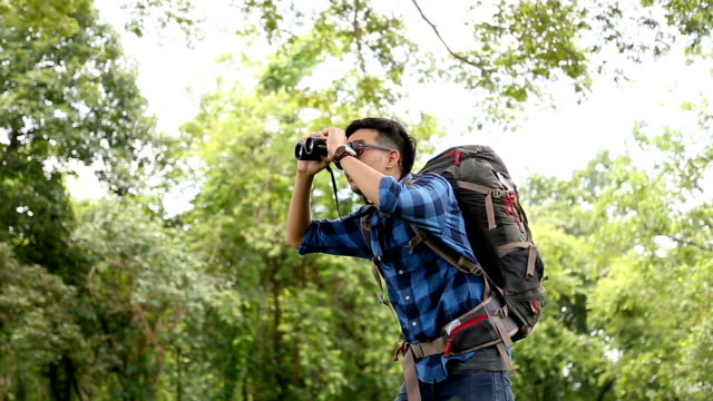 BirdWatching. Excited young man BirdWatcher use binolcular in rain forest background. Chiang Mai, Thailand. video