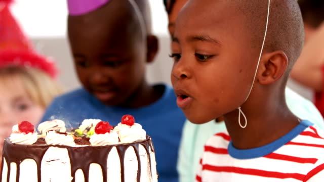 vidéos et rushes de garçon souffle les bougies d'anniversaire - fête de naissance