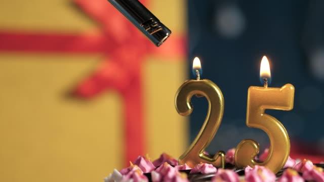 geburtstagstorte nummer 25 goldene kerzen brennen von feuerzeug, blau erdhintergrund geschenk gelbe box mit rotem band gebunden. nahaufnahme und zeitlupe - zahl 25 stock-videos und b-roll-filmmaterial