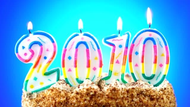 vídeos y material grabado en eventos de stock de pastel de cumpleaños con una vela de cumpleaños en llamas. número 2010. el fondo cambia de color - 2010 2019