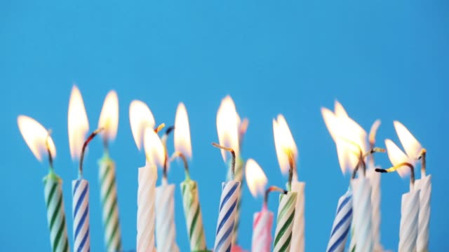 birthday candles burning over blue background video