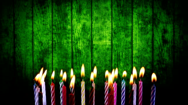 birthday candles light on green wood background
