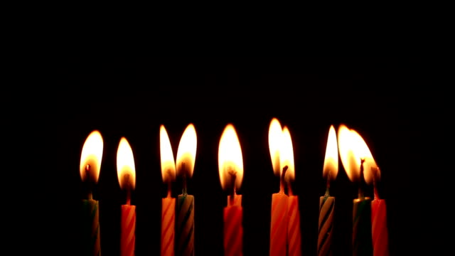 Bидео birthday candles light on isolated black