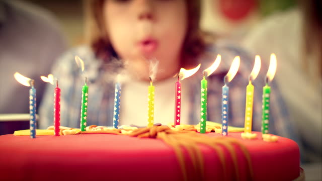 stockvideo's en b-roll-footage met slo mo birthday candles on the cake being blown out - feest
