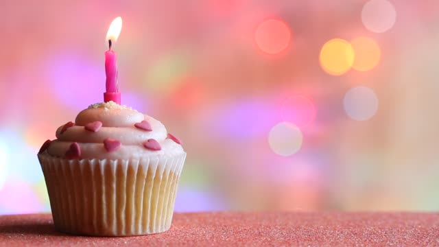 Birthday cupcake and candle on colorful defocused background party concept Birthday cupcake and candle on colorful defocused background party concept closeup happy birthday stock videos & royalty-free footage