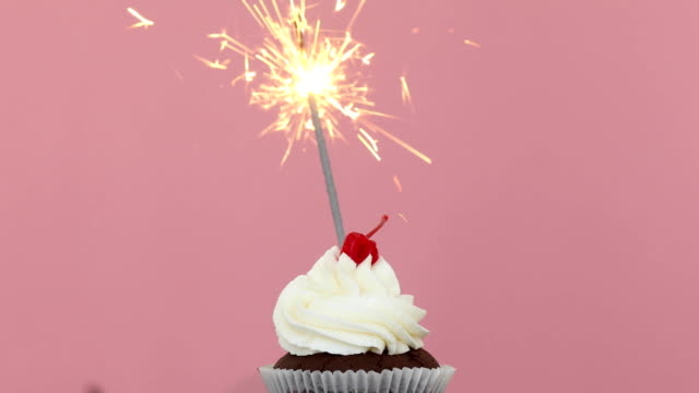 線香花火ピンク背景の誕生日ケーキ - カップケーキ点の映像素材/bロール