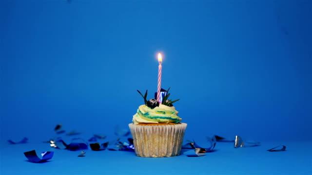 青い背景の上に3つの燃えるろうそくと誕生日のカップケーキ - カップケーキ点の映像素材/bロール