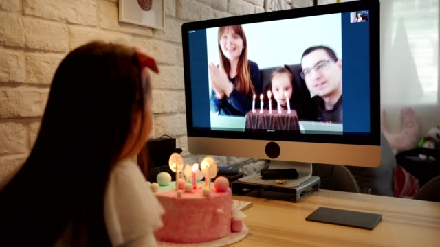 Birthday girl blowing birthday candles in home isolation while her family singing her Happy Birthday song via video app