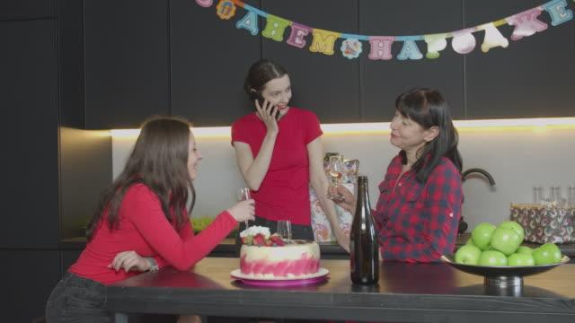 födelsedag hälsning per telefon för kvinna hemma fest - birthday celebration looking at phone children bildbanksvideor och videomaterial från bakom kulisserna