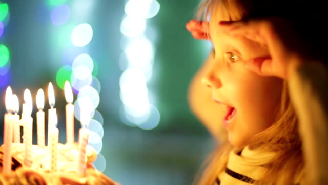 Birthday of the little girl. Slow motion. Beautiful child girl is blowing out candles on cake. Slow motion. happy birthday stock videos & royalty-free footage