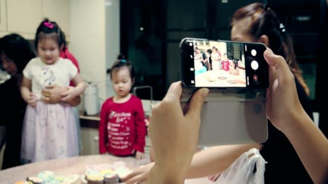 födelsedags fest hemma - birthday celebration looking at phone children bildbanksvideor och videomaterial från bakom kulisserna